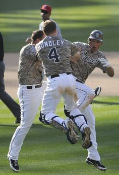 Game #42 5/20/12: Will Venable #25 of the San Diego Padres, right, celebrates with Yonder Alonso #23, left, and Nick Hundley #4 after Venable hit a game winning RBI single in the 13th inning of an interleague baseball game against the Los Angeles Angels of Anaheim at Petco Park on May 20, 2012 in San Diego, California. The Padres won 3-2. (Photo by Denis Poroy/Getty Images)