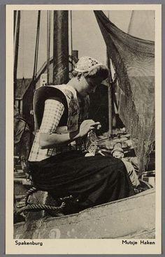 Een vrouw die een ondermuts haakt bij de mast van een botter. Ze draagt een gehaakte ondermuts, een wit gebloemde kraplap en lange lichte geruite boormouwtjes tot aan de elleboog. Ze heeft een stijf gesteven geruit bovenstuk aan het schort. 1945-1955 #Utrecht #Spakenburg