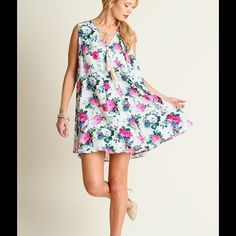 PRETTY FLORAL SWING DRESS This pretty & feminine Dress is Cream & has a lovely floral print in pink & blue. It has a front tie & is lightweight. So sweet! It's begging for heels, but flats would look cute too. Sizes S, M, L. Cotton/Polyester. No trades. Dresses