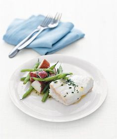 Poached Halibut With Potatoes and Green Beans | Surprisingly simple to prepare, this tasty dish is sure to go into heavy rotation. After boiling the potatoes and green beans, then tossing them with a bit of butter and chopped fresh chives, you'll poach the halibut in a dry white wine until the fish is opaque, giving each piece a wonderfully flaky texture and mild flavor. (Bonus: There's wine leftover to drink with dinner.) The meal's a bit Nord...