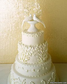 Dove Cake Topper    Millinery birds are framed by an arbor of white silk lily-of-the-valley and maidenhair fern, images that are repeated in the royal-icing decorations on this classic white cake. The doves perch on a bead-covered birdbath.