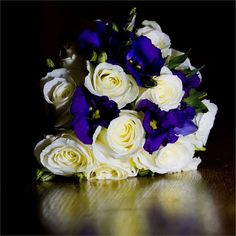 <p>Emma's gorgeous wedding bouquet was created by a different florist to the one who took care of the decor. It consisted of cream roses and purple lisianthus, whilst the bridesmaids carried pomanders of cream carnations.</p> <p>Taking care of the decor was Mountains Country House's resident florist, Helen Tinworth. She incorporated striking peacock feathers into floral arrangements, and decorated the hurricane lamps on each table with floral wreaths.</p> <p>Emma walked down the ...
