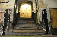 Empfangskomitee:  Die schwarzen Papier-Silhouetten der Soldaten mit Gewehr und Bajonett stehen Spalier. Viele Räume sind nachträglich mit Graffiti versehen worden. Über diese Treppe betreten Besucher das Hauptgebäude des ehemaligen Gefängnisses.