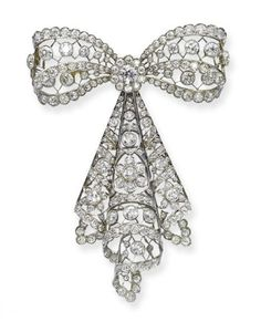 A BELLE EPOQUE DIAMOND BOW BROOCH The bow and tassel of openwork lattice design set with old-cut diamond collet and flower motifs, to the scalloped border, circa 1910, 8.0 cm long
