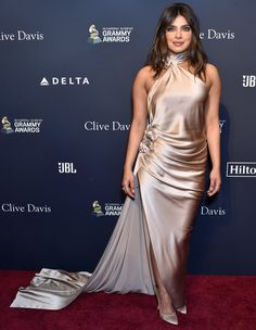 See Priyanka Chopra's Sexy High-Neck Gown to the Pre-Grammys Gala Backless Gown, Sheer Dress, Satin Dresses, Gowns, Priyanka Chopra Red Carpet, Silver Metallic Dress, Silver Pumps, Gold Dress, Glamour