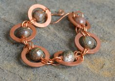 "Earth-tone agates wire wrapped inside of large copper washers and linked together. Approximately 7"" in length with a handmade hook-and-eye clasp."