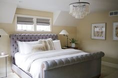 Simple gray master bedroom with tufted bed. Agate artwork and restoration hardware glam chandelier