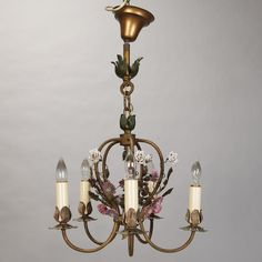 Circa 1930s French brass chandelier has five candle style lights, twisted and curved arms, and porcelain flowers in white, yellow, pink and lavender. Description from judyfrankelantiques.com. I searched for this on bing.com/images