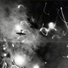 A British Lancaster bomber is silhouetted against flares and explosions during the attack on Hamburg, Germany, on the night of January 30, 1943