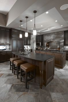Ideas for the kitchen- love the 2 separate islands; one for food prep, one for eating at. Ceiling is awesome, so is the stove area (stone). Like the dark cabinet color... don't care for the islands being a different wood color. Needs some color. Too much grey.