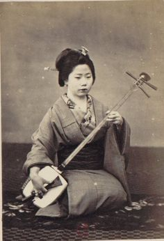 "Woman with shamisen (三味線?, literally ""three strings"") musical  instrument. Nagasaki. Japan. 1870. S)"