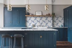 This imposing dark blue shaker style kitchen wows with a geometric Bert & May tiled wall, gorgeous Marble worktop and a surprise yellow larder interior.