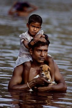C'est ça un père ! / A Father carries his daughter and her puppy through deep monsoon flood waters. / Photo by Steve McCurry.