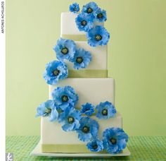 four-tiered, square fondant #cake accented with green fondant ribbon trim and bright blue sugar poppies by Ana Parzych Custom Cakes