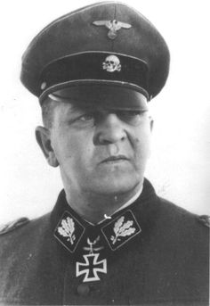 Theodor Eicke  Kommandant at Dachau (1933-1934.)  One of the most brutal men in the concentration camp system, he became the Inspector of Concentration Camps, after his stint at Dachau.  He later served in the SS Totenkopf Division and assumed command of that formation.  He was a winner of the Knight's Cross with Oak Leaves; he was killed when his aircraft was shot down in Russia on February 26, 1943.