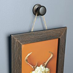 Nails aren't the only way to hang artwork. Drawer knobs and cabinet pulls add a more elegant touch. Where possible, mount the knob over a wall stud. Then install a hanger bolt with machine threads that match the knob for a solid connection.