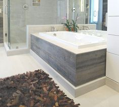 The Barn Siding is also used as the tub skirt, complementing the light tones of the wood-grain tiles. The homeowner has a strong DIY streak and made the area rug herself with leather scraps and a loom. Wood Tile Shower, Wood Tub, Shower Floor, Diy Bathroom, Bathroom Ideas, Master Bathroom, Bath Ideas, Bathroom Tubs, Silver Bathroom