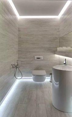 Piccolo bagno rivestito in lastre di ceramica effetto legno con una particolare illuminazione perimetrale sul pavimento e soffitto.