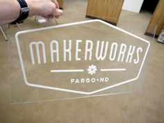 Laser cut white acrylic on clear acrylic sign.