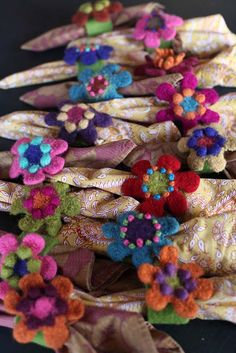 Knitted zinnias felted and made into pins and attached to napkin rings for Thanksgiving. Fun