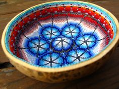 Huichol Indian Prayer Bowl (Beth Hemmila of Hint Jewelry blog), the Huichol Indian artist uses tiny seed beads size 14 (smaller then most beaded Huichol art which uses size 11) and applies them to a beeswax coating on the inside of a hollowed out gourd bottom.
