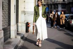 A white maxi dress is paired with platform sandals and an olive green Balmain blazer