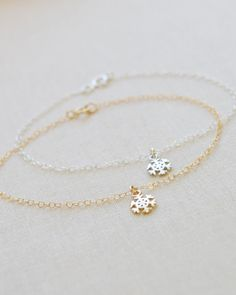 An adorable snowflake charm bracelet makes a great winter accessory. Choose from silver or gold. By Olive Yew.