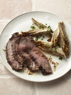 2 tablespoons whole grain mustard, plus more for serving  2 tablespoons olive oil  1/2 cup maple syrup  3 tablespoons red wine vinegar  Kosher salt and freshly ground pepper  1 1/2 pounds flank steak  4 small heads endive  1 teaspoon fresh lemon juice  Fresh parsley, for garnish