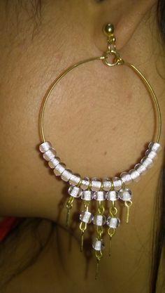 Brincos grande de argola dourada com miçangas transparentes com fundo branco. R$ 10,99
