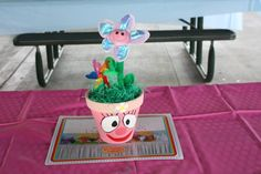 Yo Gabba Gabba Centerpiece (Foofa).  Yo Gabba Gabba characters made with terra cota pots, acrylic paint, painted Yo Gabba Gabba characters by hand, used square foam and cut to fit inside the pots, added Easter grass, and stuck the fake flowers and mini pinwheels into the foam.
