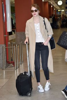 Emma Stone gives us our latest travel style inspiration courtesy of her black jeans, J Brand henley and Adidas stan smiths, topped off with a classic trench.