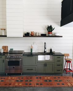 Olive green cabinets and a shiplap-covered range hood, from Jenny Komenda at Little Green Notebook, make for a family-friendly and sophisticated space.