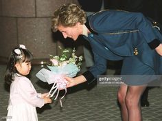 Britain's Princess Diana (R) is presented a bouquet of flowers by Hikari Shimizu, 4, upon her arrival at the headquarters of the Japanese Red Cross in…