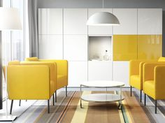 A living room with yellow armchairs, a white round coffee table and white storage with some yellow doors