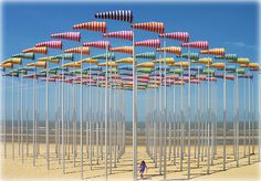 Le Vent souffle où il veut (2009) - Installation by French artist Daniel Buren. 100 flagpoles with 100 windsocks on the beach of De Haan, Belgium. This would be so good in Wellington...
