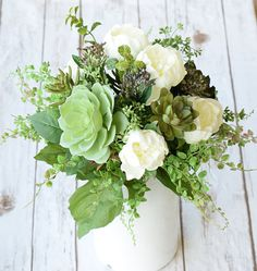 This is a Breathtaking Silk Flower Arrangement, perfect for adding a focal point to any room. Beautiful Natural Touch Succulents and Sprays, mixed with Off White English Roses.  Arranged in a fresh hand picked and elegant style. We will make this arrangement for you so the details can be customized. We can use other color Roses or mix in other flowers.  This striking centerpiece would be a perfect gift and we can drop-ship directly to the recipient if needed with a Gift Card Note Enclosed…