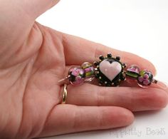 This small but beautiful set of 5 handmade lampwork beads was adapted from my ever popular original Last Tango set and includes a button shaped focal bead and two sets of perfectly matched pairs. Black with ruby pink and variegated green. The button focal measures 21mm, the encased floral beads measure 7x10mm and the encased stripes measure 6x10mm. Temporarily strung with Czech silver lined seed beads. #SB506    Hippkitty Beads, handmade by me, Vickie Miller, in my home studio, of Italian…