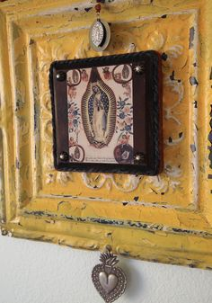 Rustic folk art wall art features an antique tin ceiling tile as the base, adorned with a leather trimmed image of the Virgin of Guadalupe, a vintage milagro ex voto, and a vintage medal of Our Lady of Guadalupe