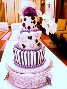 3-tier Mad Hatter wedding cake covered in white fondant decorated with black fondant stripes, hearts & polka dots, silver horse shoes, purple pearlised fondant bollas & fresh purple flowers & white orchids by Charly's Bakery, via Flickr.  I absolutely love this <3
