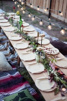 Reclaimed wood with floral decorations in Outdoor & Alfresco Dining Rooms. An outdoor table with festoon lights with an informal selection of rugs and cushions, perfect for picnics.