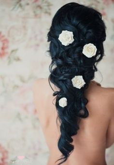 picture of bride with jet black hair with contained curly loose hair with white floral decoration