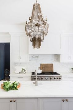 Alyssa Rosenheck - Amanda Barnes Interior Design - White and gray kitchen features a Arteriors Maxim Chandelier illuminating a gray center island fitted with a prep sink and a satin nickel gooseneck faucet.