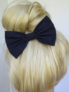 blonde hair in a bun with a black bow