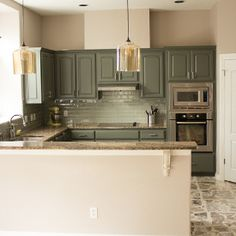 See how we transformed an outdated kitchen by painting the cabinets, replacing the backslash and  adding some pretty lighting!