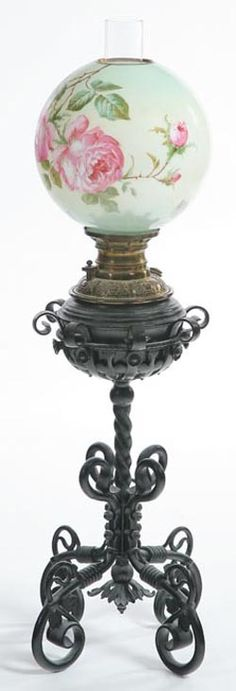 A Bradley and Hubbard piano lamp, twisted wrought iron pedestal on four scrolled feet. Brass font and milk glass shade has hand painted roses. Connecticut, circa 1885-1925