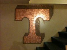 "I wanted to cover a wall in pennies. As I was sorting through a 5 gallon jug of them, I had the idea to make a design out of the shiny new pennies and cover the rest of the wall with the old brown ones. New house + new man cave + UT VOLS ( TENNESSEE VOLUNTEERS ) fan= ""power T"". So here it is. Once I did the shadowing, I decided to stop and not cover the whole wall because I like the shadowing!"
