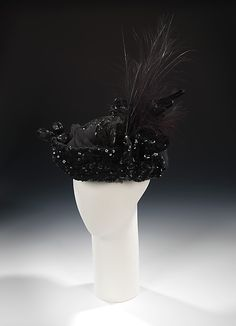 1915 evening toque. In this one, an elaborate combination of materials, including various shapes of sequins, paillettes and beads, is employed to create a glamorous effect. The highly textured and glittering surface is complemented by the vigorous burst of egret feathers.
