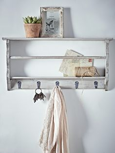 Perfect for your hallway or kitchen space, this handy storage unit has been carved from fir wood with a distressed grey washed finish. Each wall rack includes six handy metal hooks along the bottom, a rail along the middle and a slim shelf at the top. Use in your hallway for holding your keys, post and scarves, or in the kitchen for your recipe books, apron and tea towels. Each wall rack includes two picture hooks on reverse making it easy to mount onto your wall.