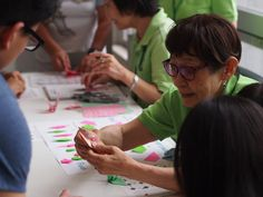 A lady learning visitors at Hiroshima peace memorial museum how to make origami cranes (orizuru).
