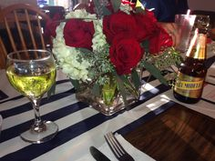 Red roses and white hydrangea centerpieces with navy blue and white striped runners.